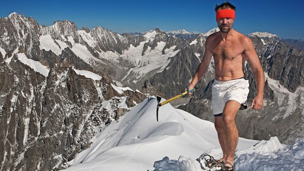 Wim Hof wearing a red headband, white shorts and carrying a pickaxe standing atop Mount Everest in the snow