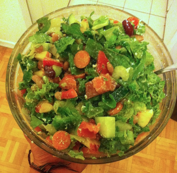 A big salad with lettuce, carrots, tomatoes, celery, cheese, beans and more in a glass bowl
